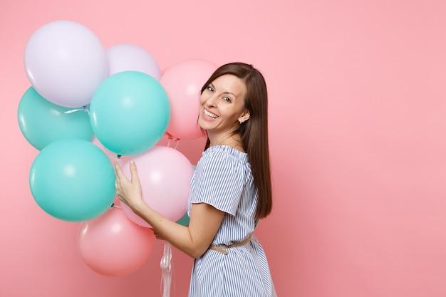 Portrait d'une jolie jeune femme heureuse en riant vêtue d'une robe bleue tenant des ballons à air colorés isolés sur un fond rose tendance brillant. fête d'anniversaire, concept d'émotions sincères.