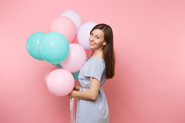 Portrait d'une jolie jeune femme heureuse souriante vêtue d'une robe bleue tenant des ballons à air colorés isolés sur un fond rose tendance brillant. fête d'anniversaire, concept d'émotions sincères.