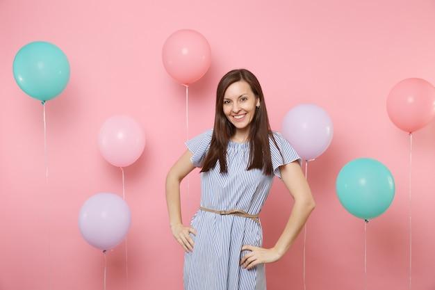 Portrait d'une jolie jeune femme heureuse souriante vêtue d'une robe à rayures bleues, debout près de ballons à air colorés sur fond rose tendance brillant. fête d'anniversaire, concept d'émotion sincère.