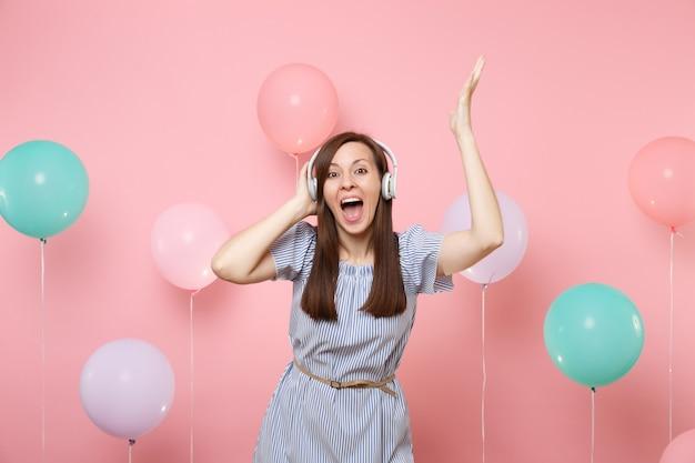 Portrait d'une jolie jeune femme joyeuse avec la bouche ouverte avec des écouteurs portant une robe bleue écoutant de la musique levant les mains sur fond rose avec des ballons à air colorés. concept de fête d'anniversaire.