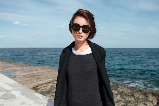 Portrait de jolie jeune femme à lunettes de soleil et veste noire au bord de la mer à l'automne