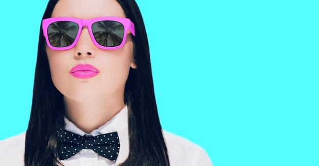 Portrait d'une jolie jeune femme à lunettes de soleil