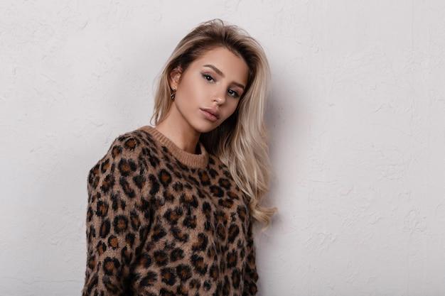 Portrait de jolie jeune femme mignonne avec de beaux yeux avec un maquillage naturel avec des lèvres sexy dans un pull léopard élégant