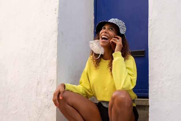 Portrait d'une jolie jeune femme noire assise et parlant avec le téléphone mobile à l'extérieur avec son masque.