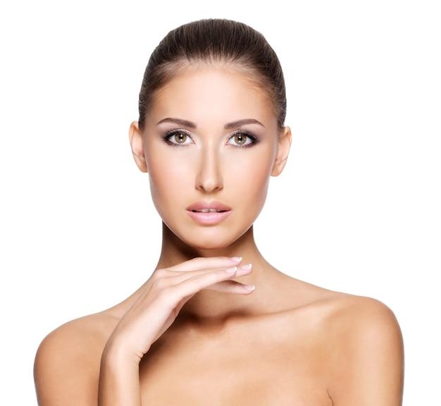 Portrait d'une jolie jeune femme à la peau claire et fraîche voulant toucher son visage