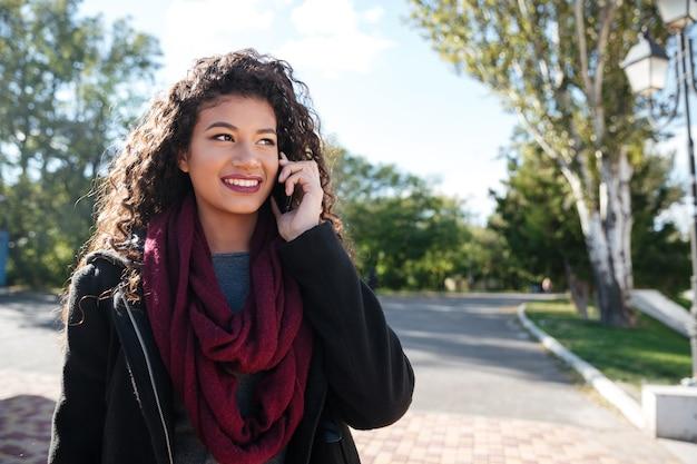 Portrait d'une jolie jeune femme à la peau foncée vêtue d'un pull et d'une écharpe parlant au téléphone. regarder de côté.