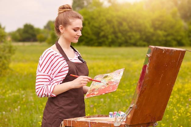 Portrait de jolie jeune femme portant une chemise blanche à rayures rouges et tablier marron