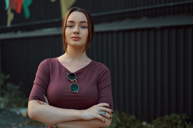 Portrait de jolie jeune femme posant contre un mur sombre