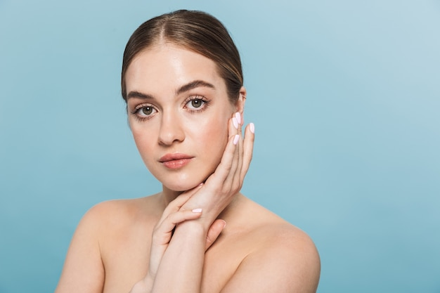 Portrait d'une jolie jeune femme posant isolée sur mur bleu.