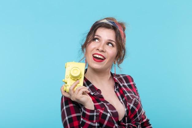 Portrait d'une jolie jeune femme positive dans une chemise à carreaux tenant un appareil photo vintage film jaune posant sur une surface bleue