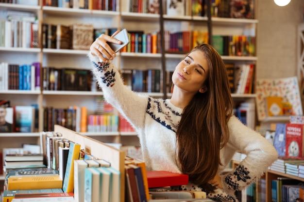 Portrait d'une jolie jeune femme prenant selfie avec téléphone portable dans la bibliothèque