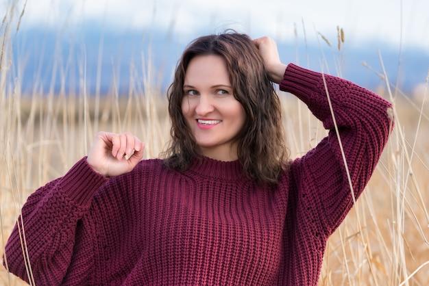 Portrait de jolie jeune femme en pull marron se dresse dans l'herbe séchée dans le champ. jolie femme de race blanche avec de longs cheveux bruns bouclés et des lèvres rouges.