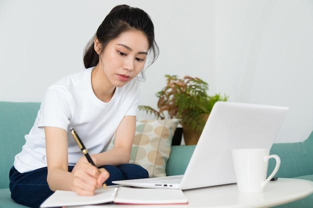 Portrait d'une jolie jeune femme qui étudie assis à la table avec un ordinateur portable à la maison