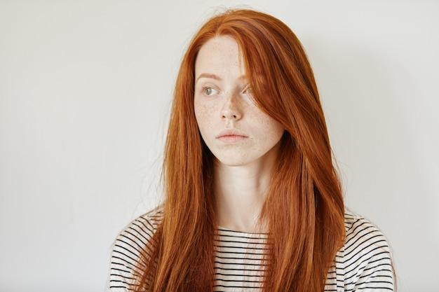 Portrait de jolie jeune femme de race blanche rousse avec des taches de rousseur et de longs cheveux lâches posant