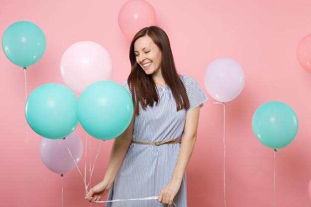 Portrait d'une jolie jeune femme riante aux yeux fermés en robe bleue tenant des ballons à air colorés sur fond rose tendance lumineux. fête d'anniversaire, concept d'émotions sincères.