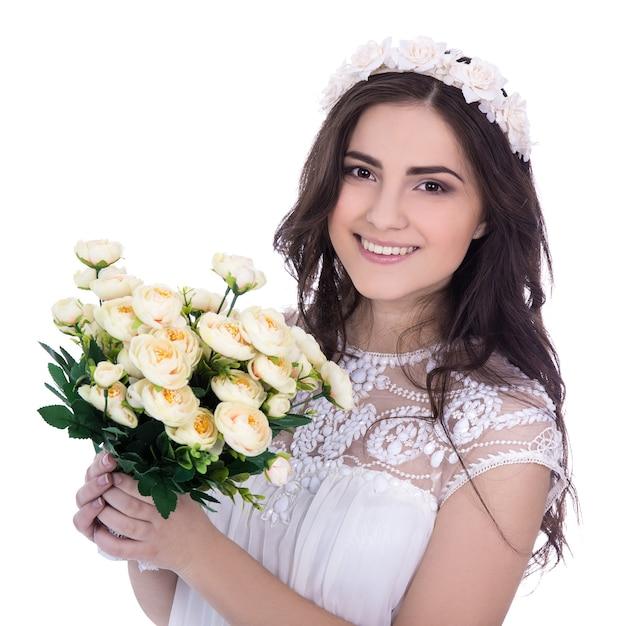 Portrait de jolie jeune femme en robe blanche avec des fleurs isolé sur fond blanc