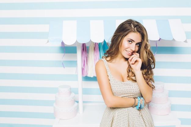 Portrait jolie jeune femme en robe d'été, avec de longs cheveux bouclés brune souriant sur un mur rayé. couleurs bleues, humeur joyeuse, exprimant la positivité.
