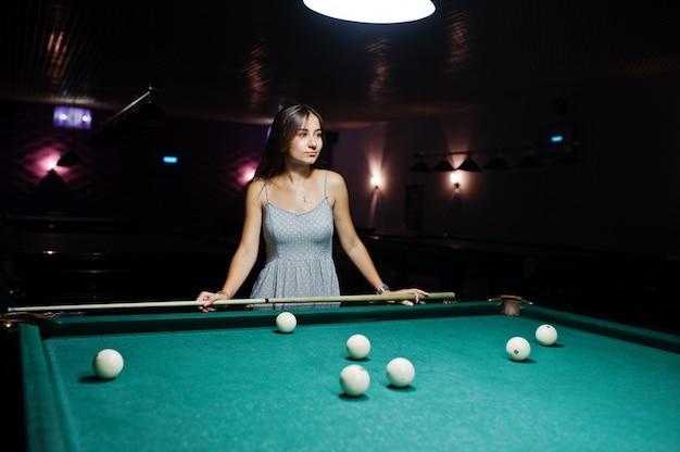 Portrait d'une jolie jeune femme en robe de jouer au billard.