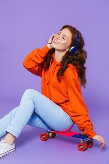 Portrait d'une jolie jeune femme rousse assise sur une planche à roulettes sur violet, écoutant de la musique avec des écouteurs