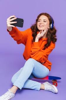 Portrait d'une jolie jeune femme rousse assise sur une planche à roulettes sur violet, écouter de la musique avec des écouteurs, prendre un selfie