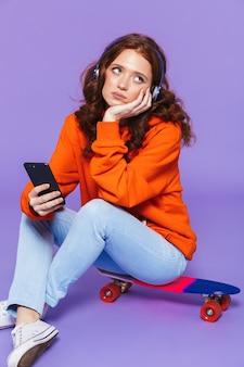 Portrait d'une jolie jeune femme rousse bouleversée assis sur une planche à roulettes sur violet, écoutant de la musique avec des écouteurs
