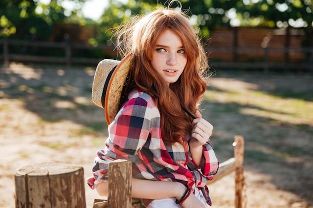 Portrait de jolie jeune femme rousse cowgirl debout à l'extérieur