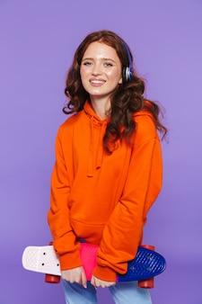 Portrait d'une jolie jeune femme rousse debout sur violet, tenant une planche à roulettes, écoutant de la musique avec des écouteurs