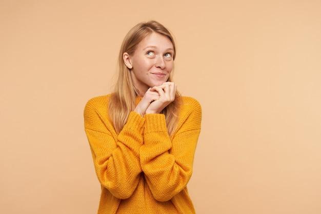 Portrait de jolie jeune femme rousse avec un maquillage naturel en gardant les mains jointes sous son menton et regardant positivement vers le haut, isolé sur beige