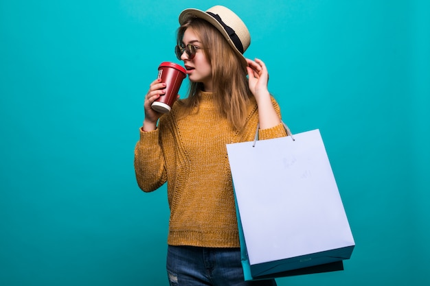 Portrait de jolie jeune femme avec des sacs à provisions et tasse de papier de café frais