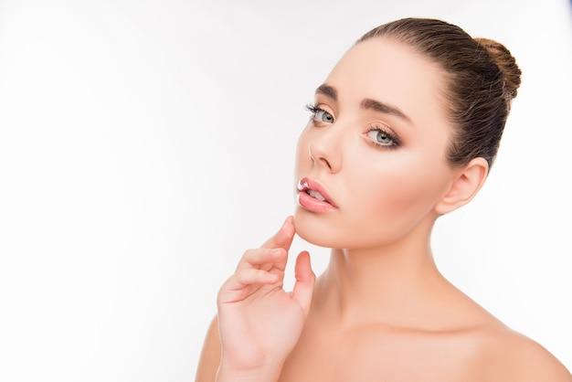 Portrait de jolie jeune femme sensuelle touchant son menton