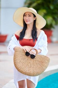 Portrait d'une jolie jeune femme souriante en chapeau de paille, bikini et chemise en coton blanc debout à la piscine avec sac en osier et lunettes de soleil dans les mains