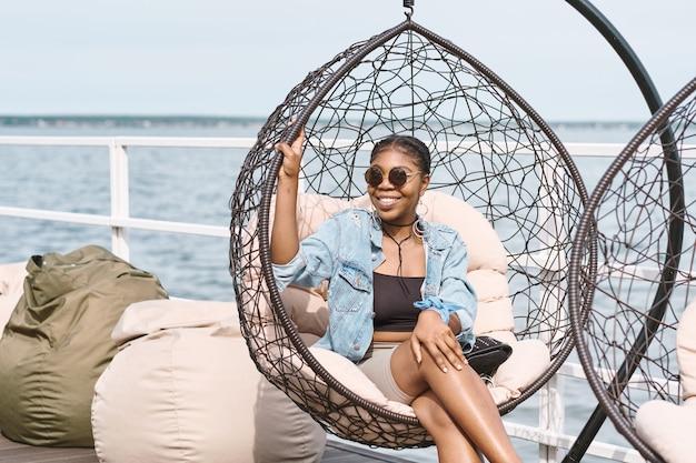 Portrait d'une jolie jeune femme souriante à lunettes de soleil relaxante dans une chaise suspendue à l'extérieur à la fête