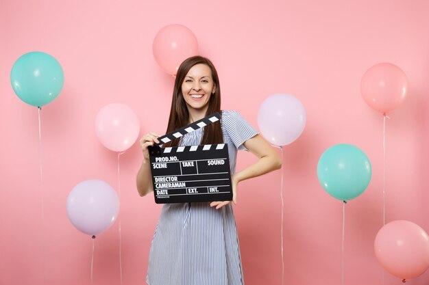 Portrait d'une jolie jeune femme souriante vêtue d'une robe bleue tenant un film noir classique faisant un clap sur fond rose avec des ballons à air colorés. fête d'anniversaire, émotions sincères.