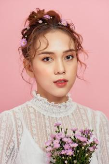 Portrait d'une jolie jeune femme tenant le bouquet et regardant par-dessus son épaule isolé sur rose