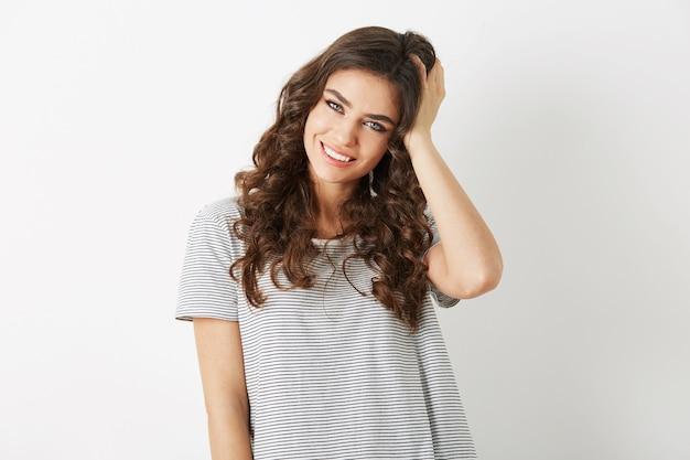 Portrait de jolie jeune femme tenant ses cheveux bouclés souriant isolé sur fond blanc studio, habillé en t-shirt, style casaual, regardant à huis clos, look naturel, beau modèle hipster