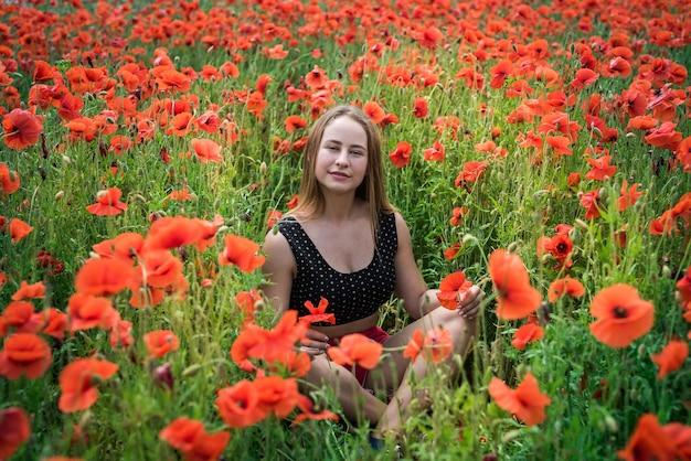 Portrait d'une jolie jeune femme en tenue de sport assis dans le champ de coquelicots en fleurs. profitez de la liberté en été