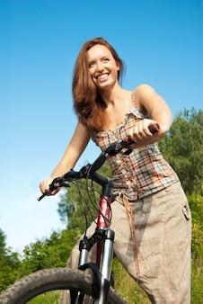 Portrait de jolie jeune femme à vélo dans un parc souriant - outdoor