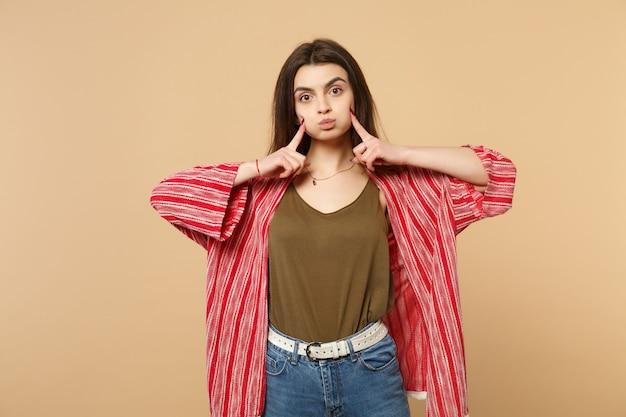 Portrait d'une jolie jeune femme en vêtements décontractés pointant l'index sur les joues soufflées, isolée sur fond beige pastel en studio. les gens émotions sincères, concept de style de vie. maquette de l'espace de copie