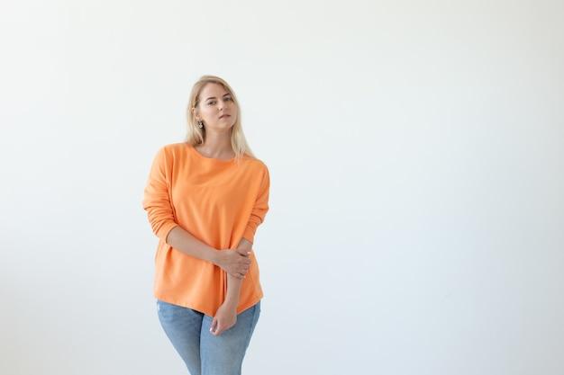 Portrait de jolie jeune femme en vêtements décontractés posant sur un fond blanc. espace de référence