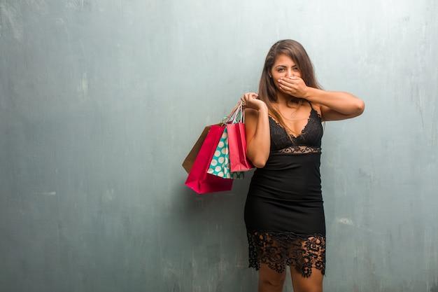 Portrait de jolie jeune femme vêtue d'une robe contre un mur recouvrant la bouche, symbole de silence et de répression, essayant de ne rien dire. tenir des sacs à provisions.