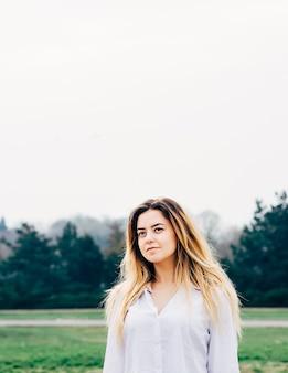 Portrait de jolie jeune fille aux cheveux longs en chemise blanche dans un parc avec fond de pins verts