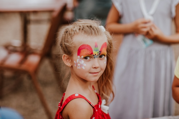 Portrait de jolie jeune fille blonde aux taches blanches avec maquillage comme une licorne