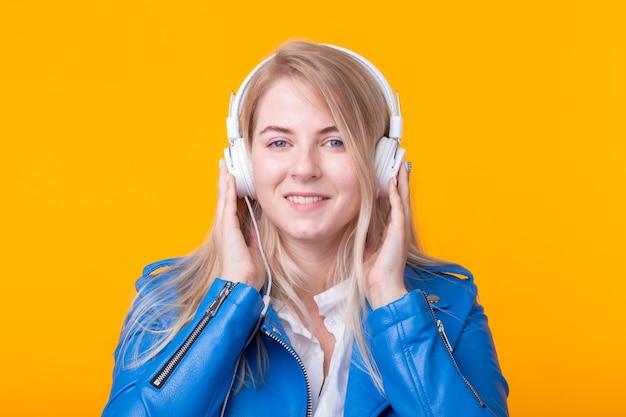 Portrait de jolie jeune fille blonde positive à l'écoute de la musique préférée dans les écouteurs en bleu