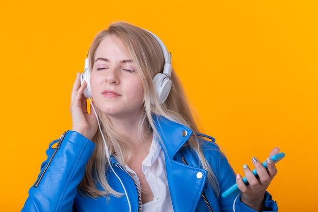 Portrait de jolie jeune fille blonde positive, écouter de la musique préférée dans les écouteurs en veste de cuir bleu posant sur le mur jaune. concept de concerts de musique et de radio en ligne.