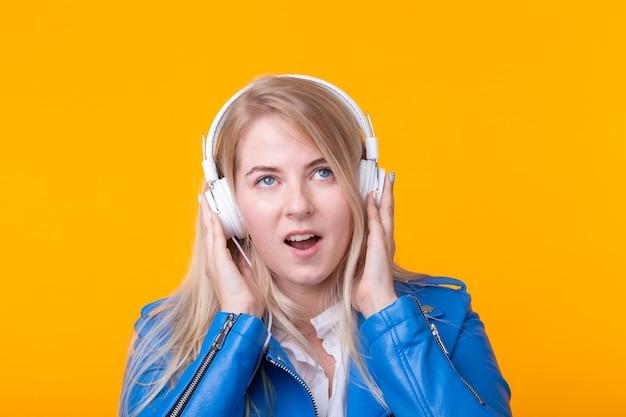 Portrait de jolie jeune fille étudiante blonde tenant le smartphone avec un casque de veste en cuir bleu posant sur un mur jaune. concept d'écoute de la radio en ligne et de l'abonnement musical.