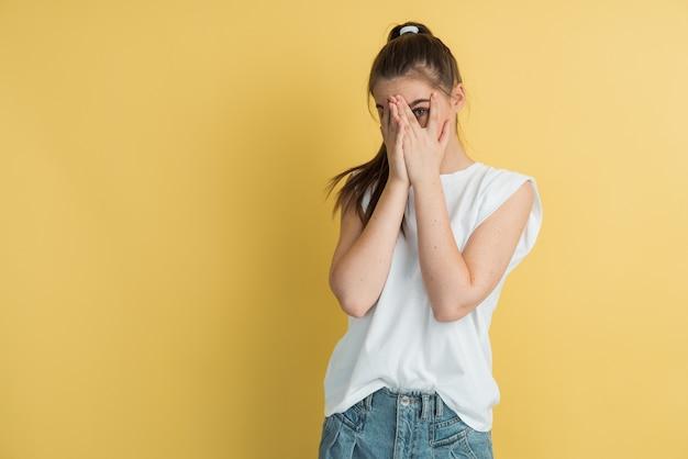 Portrait de jolie jeune fille européenne se cachant le visage avec la main regardant la caméra à travers les doigts en face de fond de studio jaune.