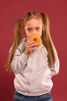 Portrait de jolie jeune fille mangeant un beignet