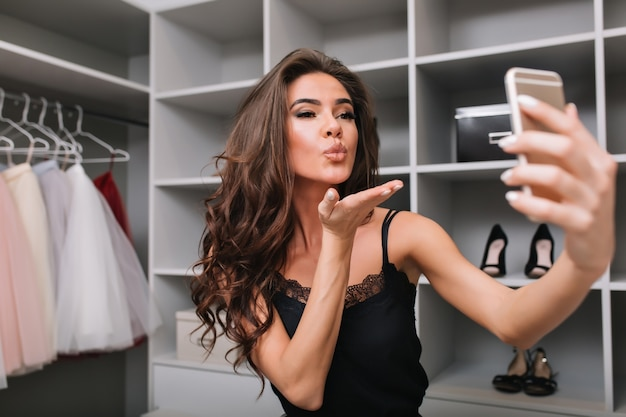 Portrait de jolie jeune fille prenant selfie à l'aide de smartphone dans une armoire, dressing. elle envoie un baiser. vêtue d'une robe élégante, a de longs cheveux bruns bouclés.