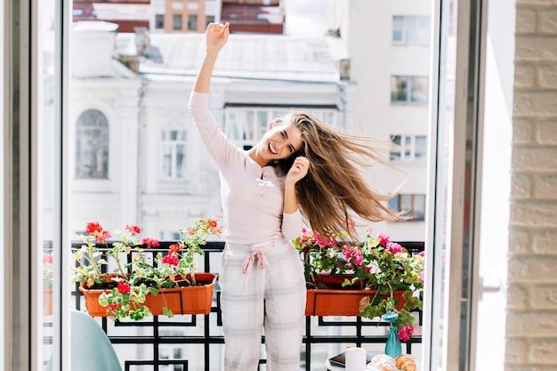 Portrait jolie jeune fille en pyjama s'amuser sur le balcon de la ville. elle bouge, lève les mains. ses longs cheveux volent et elle sourit.