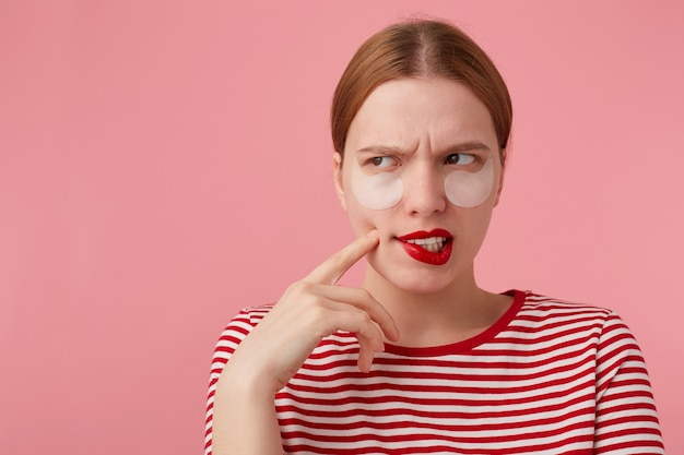 Portrait de jolie jeune fille rousse pensante avec des lèvres rouges et des taches sous les yeux, porte un t-shirt rayé rouge, se demande quelle robe porter. des stands.